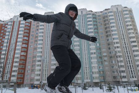 boy jumping from the mountain in the snow against the background of multi-storey buildings. winter holiday concept