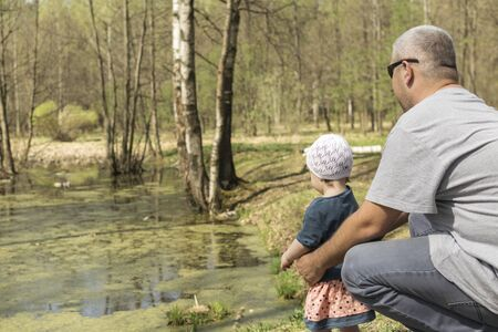 a man in a gray T-shirt squatted with a child facing a beautiful green forest lake