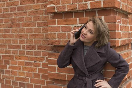 beautiful woman 30-40 years old emotionally talking on the phone near a red brick wall
