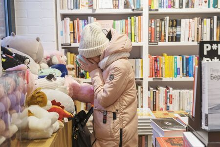 02.02.2020 Russia, Moscow, the territory of the Arma plant. a teenage girl in a bookstore buried her face in a plush toy. symbol of the passing childhood. Stock Photo