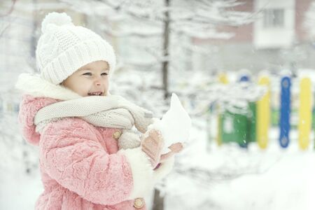 beautiful girl in a pink fur coat laughs and sculpts a snowball in a snowy yard