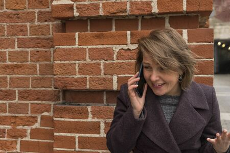 woman emotionally talking on the phone near a red brick wall. despair on face, crying, hand raised and gesturing