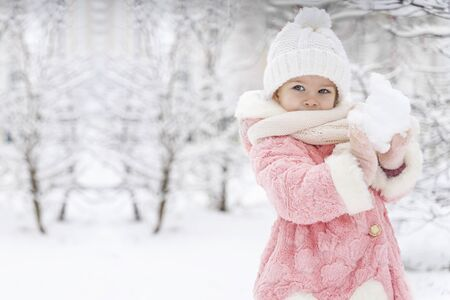 beautiful girl in a pink fur coat smiles and sculpts a snowball in a snowy yard