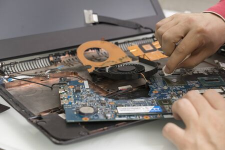 disassembled dusty laptop. the master cleans the processor Archivio Fotografico