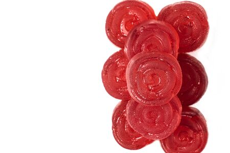 bright juicy saturated red marmalade in the form of roses closeup lies a slide on a white background isolate