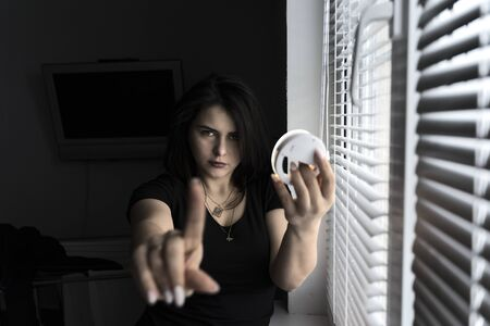 Portrait of a young beautiful brunette girl in dark colors. woman put her hand forward showing prohibitory sign. in the other hand a mirror