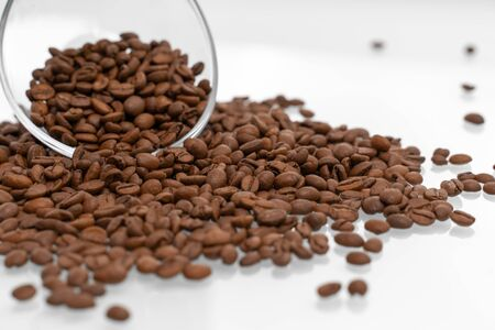 Coffee beans pour out of a glass bowl onto a light surface. coffee background, close-up