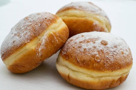 three donuts sprinkled with powdered sugar close-up