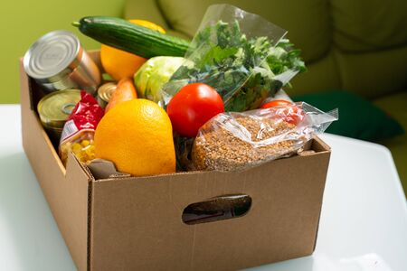products in a cardboard box are on the kitchen table. food delivery