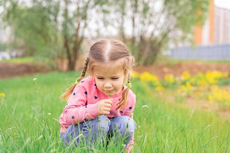 little girl sniffs the first spring flowers on a walk Imagens - 148095974