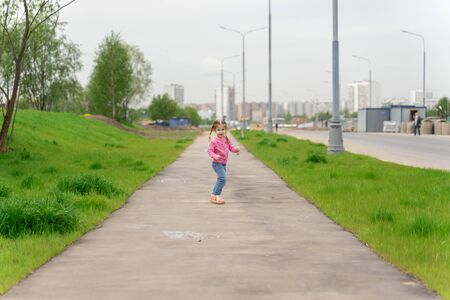 little girl runs down the street in summer and laughs 版權商用圖片