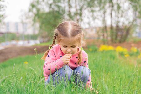 little girl sniffing flowers. child enjoys nature
