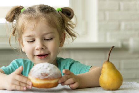 little girl chooses a donut instead of a pear. problems in baby food. obesity in children