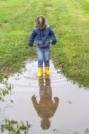 baby in rubber boots in a puddle. abundant rain puddle on the road 스톡 콘텐츠