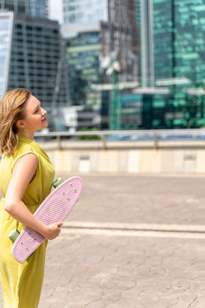 red-haired 30th beautiful woman with a skateboard dreamily looks at the skyscrapers of a big city Stock fotó