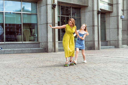 young mother exercises on a skateboard on the street, her daughter helps her mother ride a skateboard, her mother learns to ride a skateboard in a city