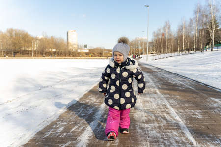 3-4 years old child walks along the wide embankment of a frozen pond in winter on a sunny day