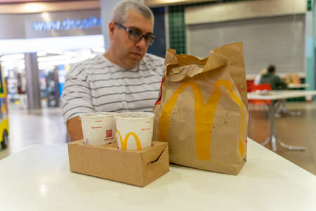 07 19 2020 Russia, Moscow.a man sits at a table in a McDonalds restaurant, in front of him is an individually wrapped food bag. rejection of common trays in restaurants due to the coronavirus.