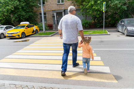 07 19 2020 Russia, Moscow. father and little daughter cross the road at a pedestrian crossing