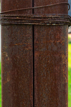 old rusty iron pole wrapped with wire. brown background