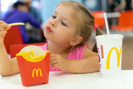 07 19 2020 Russia, Moscow.little girl eating french fries at mcdonald's