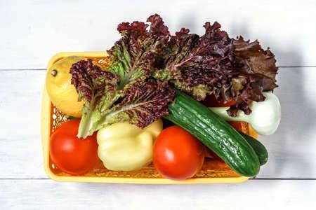 vegetables for salad in a basket on a wooden background Stock fotó