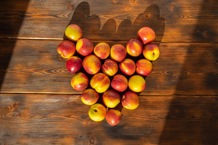 nectarines laid out in the shape of a heart on a wooden background Stock fotó