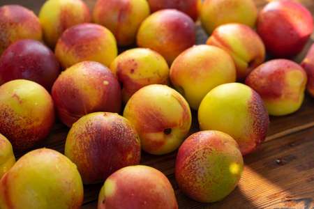 many ripe nectarines on a wooden table. harvest of nectarines