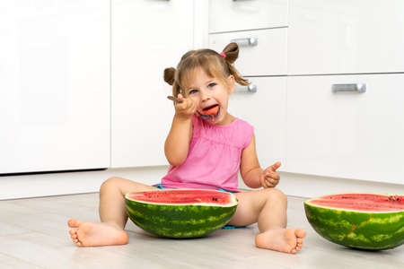 Cute baby-girl sits on a floor  and eats a water-melon with a spoon Stock fotó