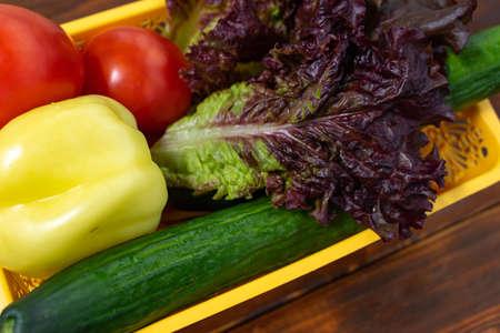 vegetables for salad in a basket on a wooden background, close-up Stock fotó