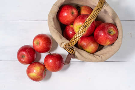 apples in a basket on a white wooden background. view from above Standard-Bild