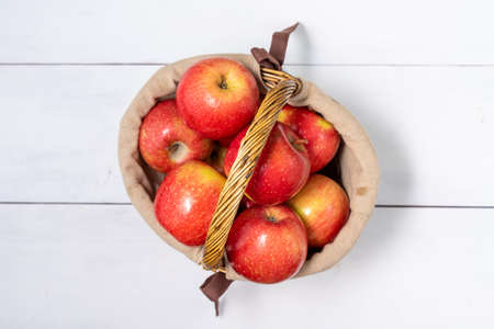 basket with ripe red social apples on white wooden background Standard-Bild