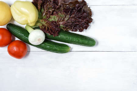 set of green vegetables on a white wooden background with place for text. tomatoes, lettuce, bell peppers, fresh onions, lemon and cucumber