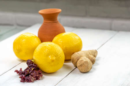 the set is antiviral. lemons, ginger root, drink in a jug and herbs on a white wooden table in the kitchen Stock fotó