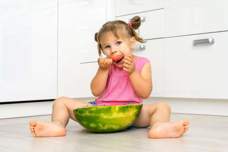 little girl 4 years old with appetite eats watermelon with a spoon sitting on the floor at home and is happy