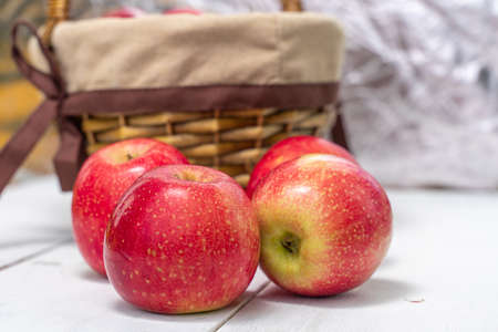 red juicy fresh apples on wooden background and basket
