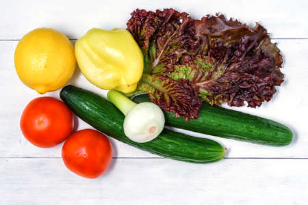 set of green vegetables on a white wooden background. tomatoes, lettuce, bell peppers, fresh onions, lemon and cucumber