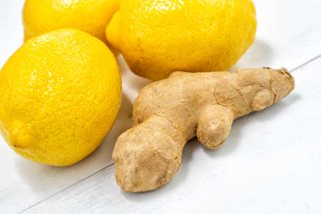 lemons and ginger root on white wooden background