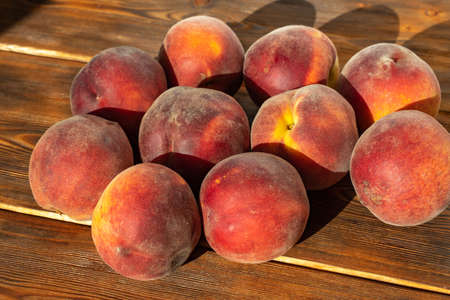 many ripe peaches on a wooden background