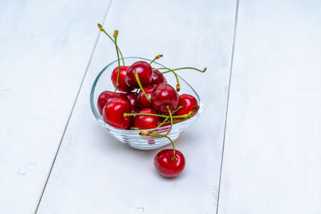ripe cherries in a glass bowl on a white wooden table