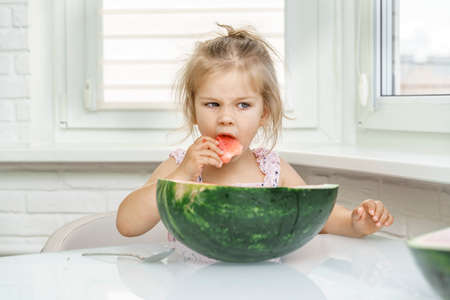cute baby eating a piece of watermelon at home Stock fotó