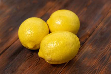 three bright yellow lemons on a wooden background Stock fotó