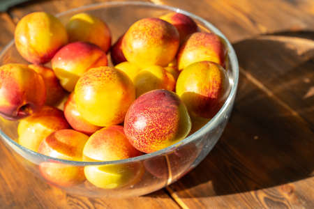 ripe juicy nectarines in a glass bowl on a wooden table on a sunny day Stock fotó