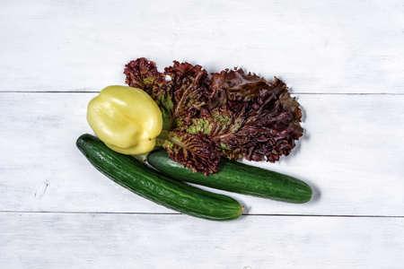 set of green vegetables on a white wooden background. lettuce, cucumber, bell pepper for salad