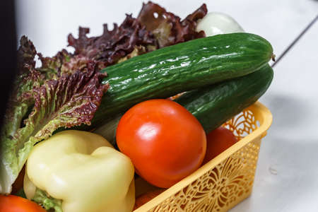 set of vegetables in a basket on a white wooden background