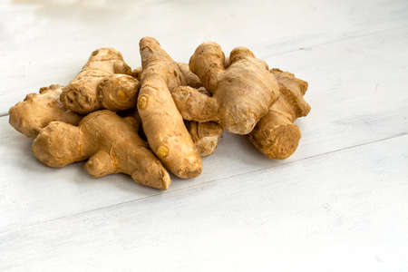 a bunch of ginger on a white wooden background. healthy food