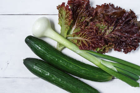 set of green vegetables on a white wooden background. lettuce, onion, cucumber for salad