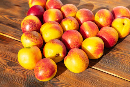 nectarines on a wooden brown background. sunny day