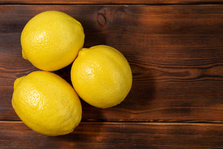 three whole yellow lemons on a wooden table, close-up