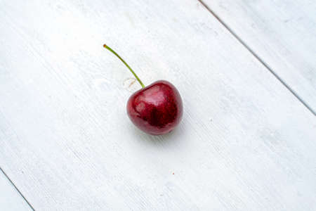 one ripe red cherries on a white wooden textured background. copy space